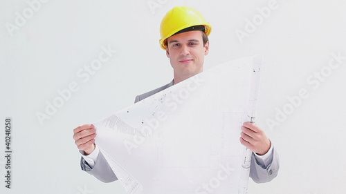 Serious businessman holding blueprints