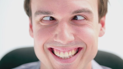 Smiling businessman sitting with crossed eyes