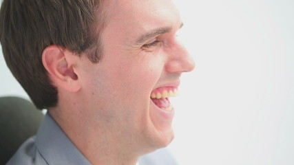 Happy man laughing while sitting on a chair