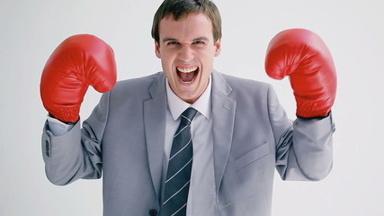 Smiling businessman wearing boxing gloves