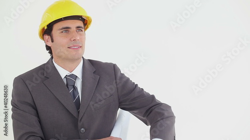 Smiling businessman reading blueprints