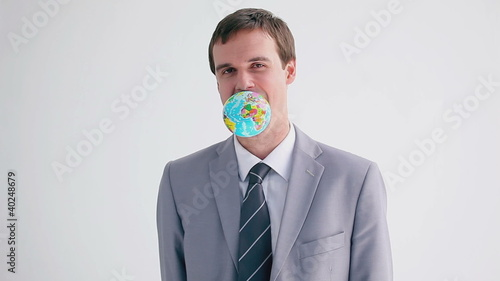 Happy executive holding a globe with his mouth