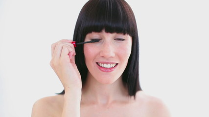 Happy woman applying mascara on her eyelashes