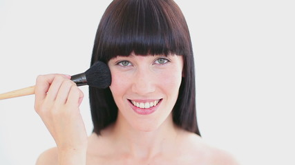 Happy brunette woman using a powder brush