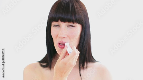 Smiling woman applying lip balm on her lips