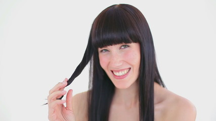 Dark-haired woman holding a strand of her hair