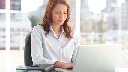 Happy businesswoman sitting while using a laptop