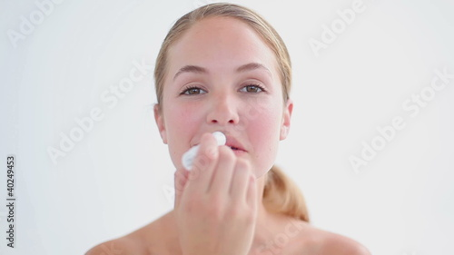 Smiling blonde woman using a lip balm