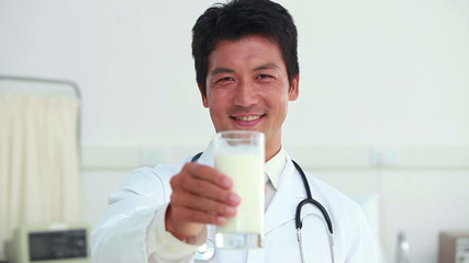Doctor showing a glass of milk