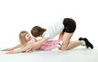 Young mother doing sport exercises with her little daughter