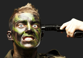 portrait of young soldier comiting suicide over black background