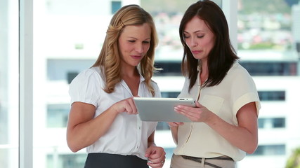 Two females workers using an eBook