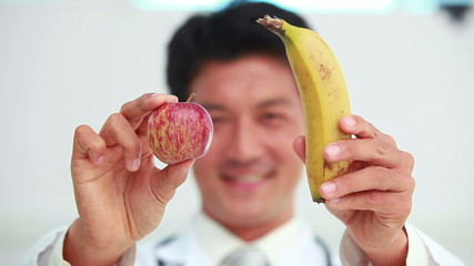 Doctor showing banana and apple