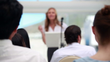 Blonde woman giving a conference