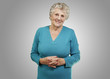 portrait of senior woman standing over grey background