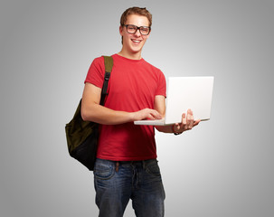 portrait of young man holding laptop and wearing backpack over g