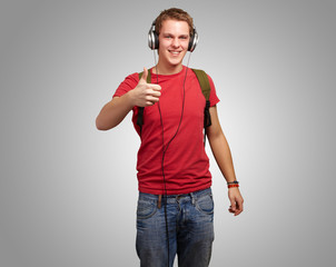 portrait of cheerful young student listening music and gesturing