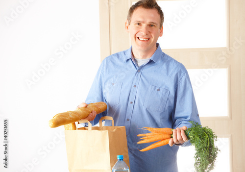 Man with shopping bag at home