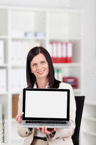 lächelnde frau zeigt bildschirm ihres notebooks