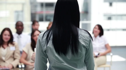 Brunette business woman speaking to business people