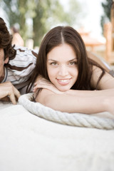 Young couple lying on sand, smiling, portrait