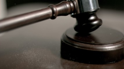 Hand pounding gavel in super slow motion