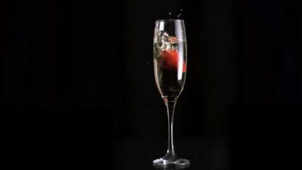 Strawberry diving into water in super slow motion in a flute