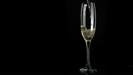 White wine poured in super slow motion in a flute glass