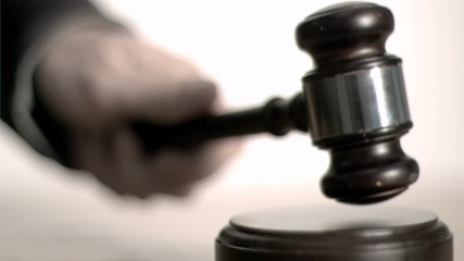 Man's hand striking in super slow motion a gavel