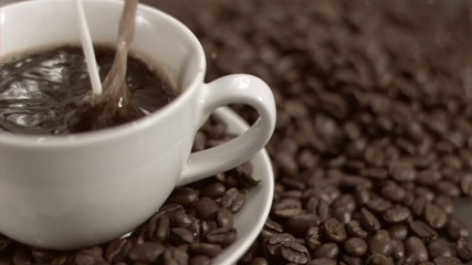 Milk flowing in super slow motion in coffee cup