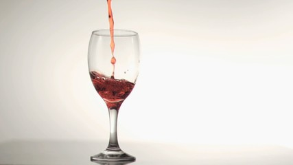 Red wine filling in super slow motion a glass of wine