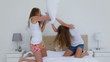 Friends in nightwear fighting with pillows