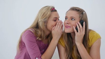 Woman receiving a call while sitting with a friend