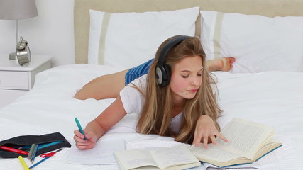Young woman listening to music while doing her homework