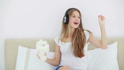 Young blonde woman listening to music with her headphones