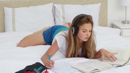 Young woman studying while listening to music
