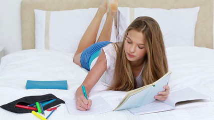 Serious young woman studying while lying