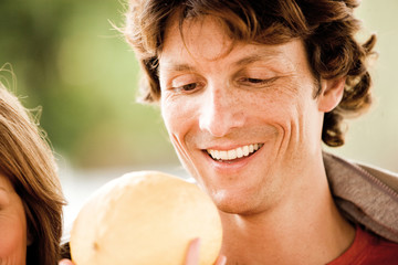Young man holding muskmelon, close-up