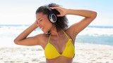 Tanned woman using headphones