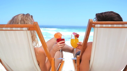 Couple on deck chairs drinking cocktails
