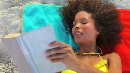 Tanned woman reading a book