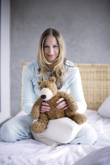 Young woman holding teddy bear, smiling, portrait