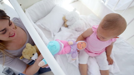 Mother playing with her baby with dolls