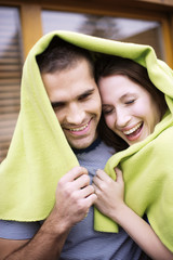 Young couple holding green cloth, smiling