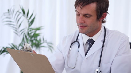 Doctor writing on a clipboard while sitting