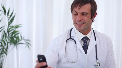 Smiling doctor sending a text message