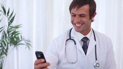 Happy doctor sending a text message
