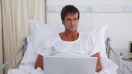 Patient using a laptop while sitting in a sickbed