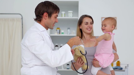 Doctor using his stethoscope on a baby