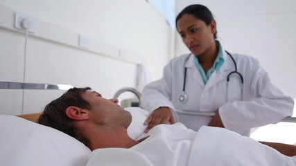 Doctor talking to a patient lies in a bed